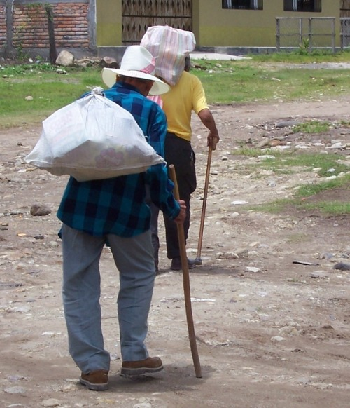 Two sponsored elderly men carry their monthly provisions back to their homes.